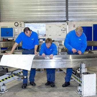 Factory workers remanufacturing a slewing bearing